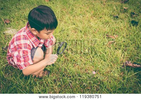 Young Boy Exploring Nature With Magnifying Glass. Outdoors In The Day Time. Retro Style.
