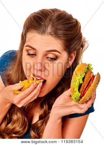 Girls eats greedily burger with two sides. Fastfood concept.