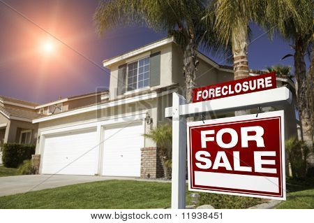 Red Foreclosure For Sale Real Estate Sign in Front of House with Red Star-burst in Sky.