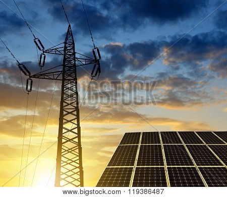 Solar panels with electricity pylon at sunset.