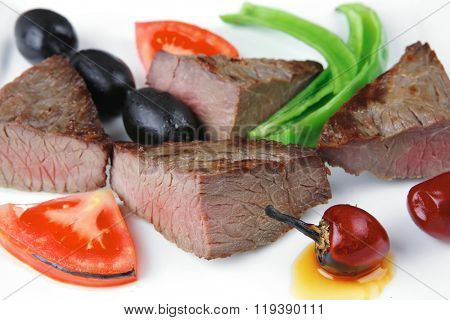 meat food roast beef fillet mignon served on white plate with apples dill and tomatoes over black wooden table