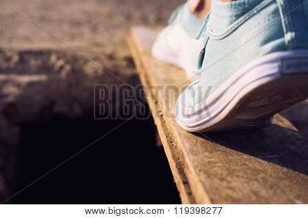 Female Feet In Sneakers Walking On A Narrow Board Above A Large Pit