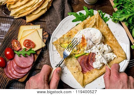 Man eating crepe galette with meat, avocado, soft white cheese and poached egg on white plate. Sliced yellow cheese, pastrami, cherry tomatoes, green salad and stack of crepes on side. Top view