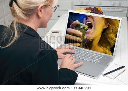 Frau In der Küche mit Laptop für Musik und Unterhaltung. Das Bild kann leicht ersetzt werden mit