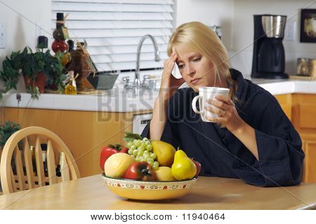 Woman with hand on her head as she gazes in thought. Head ache? Depression? Loneliness? Versatile image.