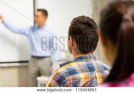 education, high school, teamwork and people concept - teacher standing in front of students and showing something on white board in classroom