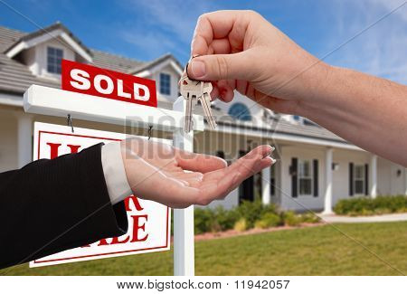 Handing Over the House Keys in Front of Sold New Home Against a Blue Sky