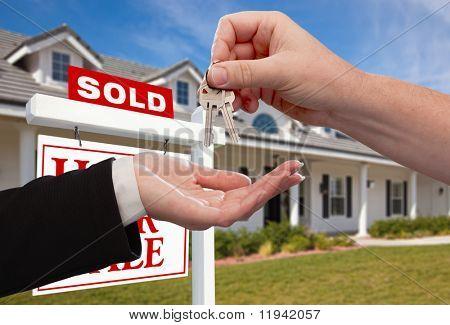 Afhalen sleutels huis voorzijde verkocht nieuwe woning tegen een blauwe hemel