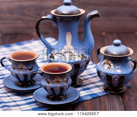 teapot and two cups of tea on a wooden background