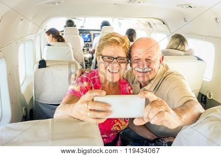 Senior happy couple taking selfie with mobile phone on board of plane - Smiling retired people having fun flying from Coron to Borakay by airplane - Concept of elderly happiness on world wide travel poster