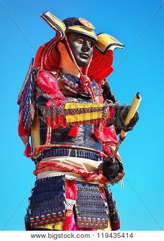 Man In Samurai Costume With Sword On Blue Sky Background. Original Character