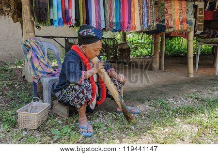 Older Thai  woman smokes through  bamboo cane