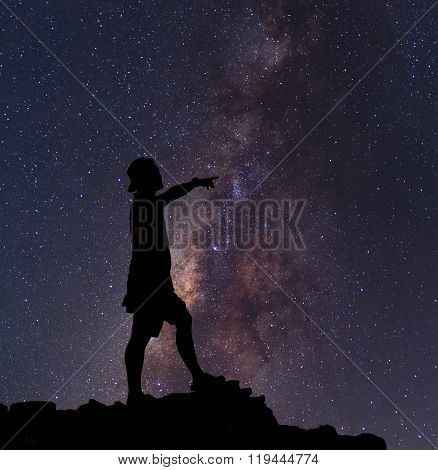 Star-catcher. A person is standing next to the Milky Way galaxy pointing on a star poster