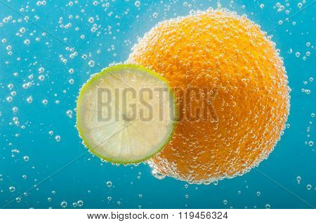 Orange And Lime Slice In Bubbles Water.