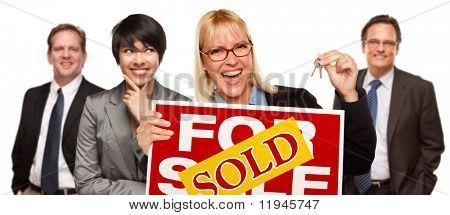 Real Estate Team achter met Blonde vrouw op de voorgrond houden toetsen en verkocht voor verkoop onroerend goed teken ik