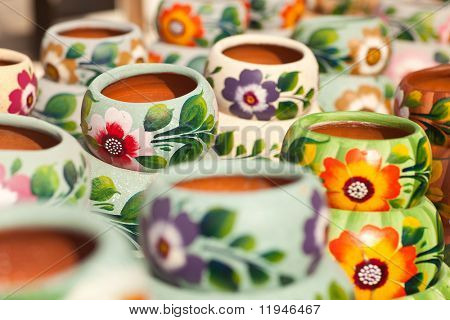 Variety of Colorfully Painted Ceramic Pots in an Outdoor Shopping Market.