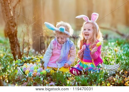 Kids On Easter Egg Hunt In Blooming Spring Garden.