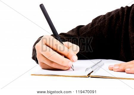 A child hand is writing with pen on a spiral notebook on white background