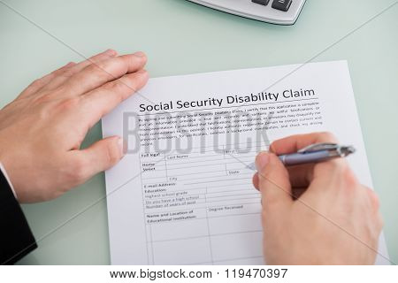 Person Hand Over Social Security Disability Claim Form
