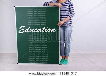 Woman in causal with green blackboard for your text, near wall