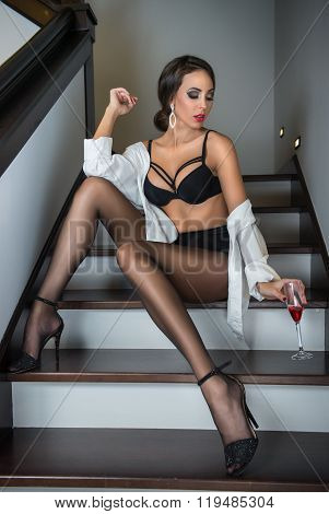 Full-length portrait of brunette woman wearing a white male shirt over black lingerie posing