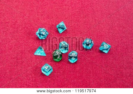 Set of blue and green specialized polyhedral dice with numbers used in role-playing games on a table with red cloth poster
