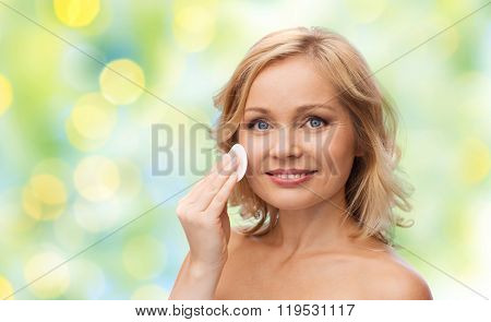 beauty, people and skincare concept - young woman cleaning face and removing make up with cotton pad over green summer lights background