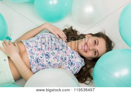 beautiful curly girl in multi-colored top, white shorts and bright shoes playing with balloons.