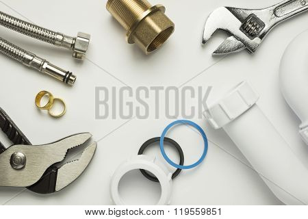 A selection of plumbing tools and fittings on a white background poster