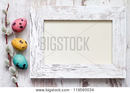 Easter eggs and empty vintage photo frame