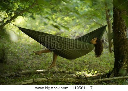 Beautiful young woman relaxing in a hammock deep in the woods.