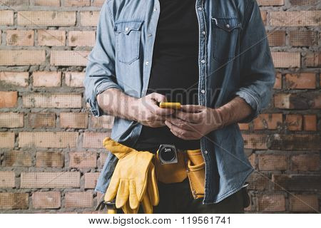 hand of carpenter with cell-phone