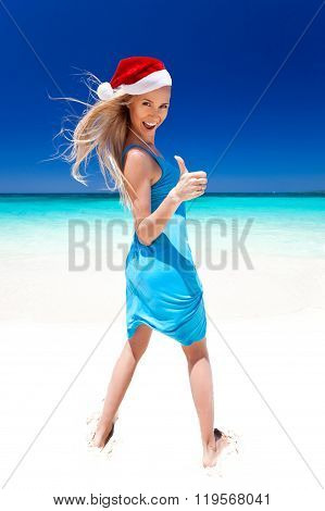 Happy blond girl in Santa hat on tropical beach showing thumbs up. Christmas Vacation