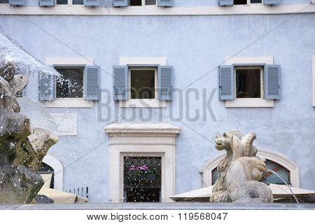 Mythological Creatures As Fountain Statues And Pale Blue House With Open Windows At The Background