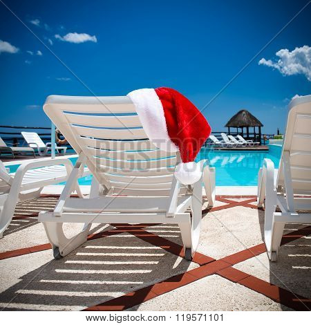 Santa Claus Hat On Lounge Sunbeds Near Swimming Pool