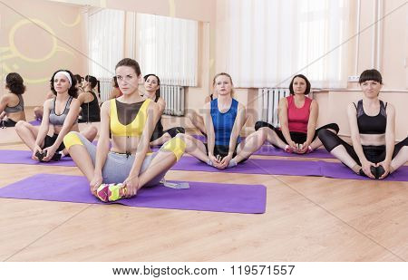 Group Of Female Caucasian Sport Athelets Having Indoors Sport Training On Mats.