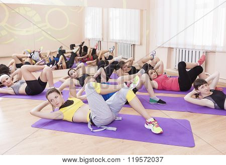 Fitness Concept And Ideas. Group Of Seven Female Athletes Performing Legs Stretching Exercise On Spo