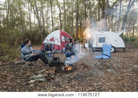 Mother and kids camping with tent and teardrop trailer