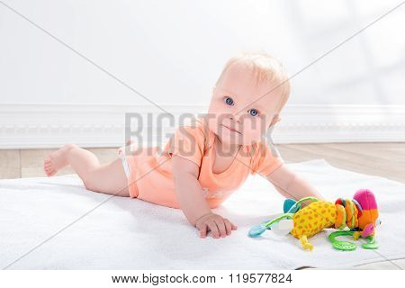 baby girl  with toy, lying on the floor