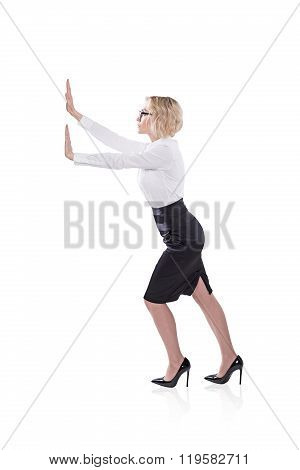 A businesswoman pushing an imaginary wall. Side view. Isolated. Concept of effort. poster