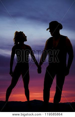 A silhouette of a woman holding on to her cowboy's hand.