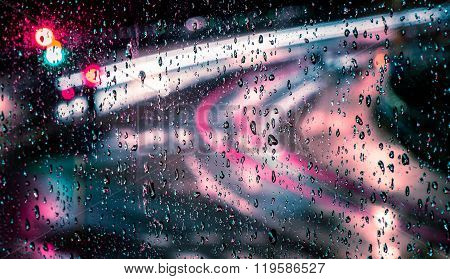 Macro photo or raindrops with trailing blurred red, pink, blue and green motion trail lights in the