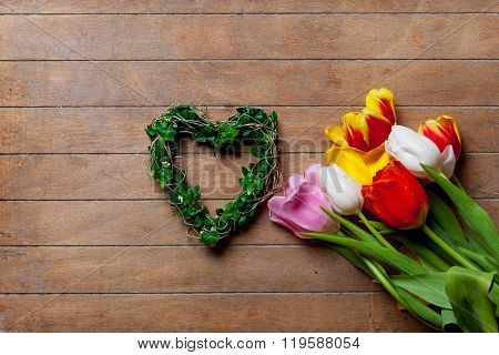 Bunch Of Tulips And Heart-shapped Wreath Lying On The Table