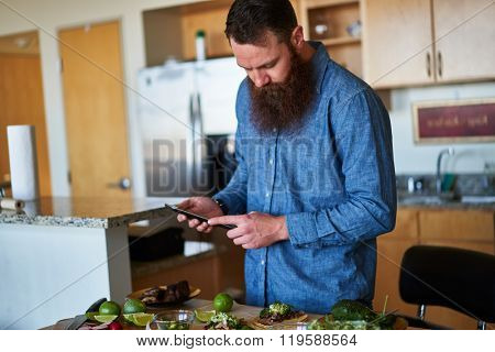 man making tacos in kitchen and using tablet to look up recipe shot with selective focus