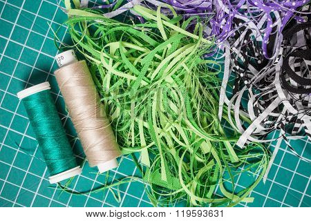 Sewing Threads And Textile Offcuts On Cutting Checkered Green Mat