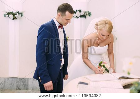 Bride And Groom On Marriage Registration. The Groom Looks At The Bride. Newlyweds At The Wedding Cer