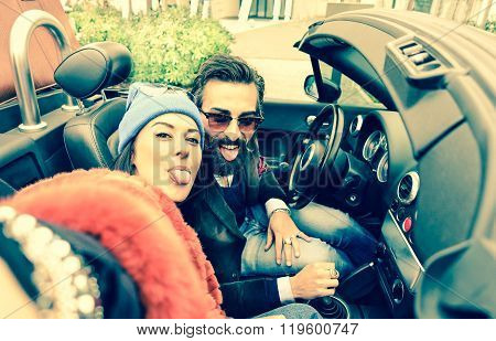Happy couple taking selfie at car trip - Young tourists having fun together traveling around Europe - Technology addiction and fashion lifestyle concept - Vintage filter with main focus on her poster