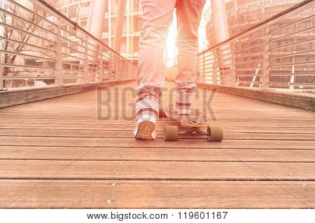 Hipster Guy In Action On Wood Bridge - Skater Boy Driving At Sunset Around City - Sport And Recreati