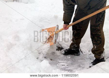 people in camoflage cleans snow shovel