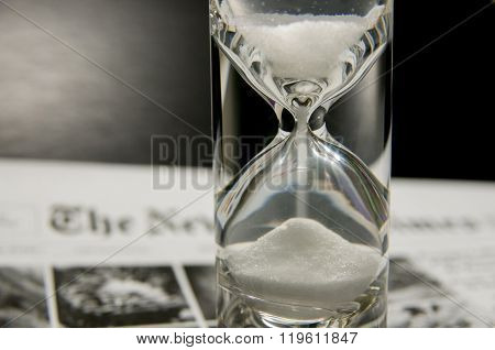 Half-filled Sandglass On Newspaper